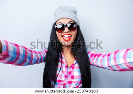 Capturing fun. Happy young African woman in funky clothes making selfie while standing against grey background  - stock photo