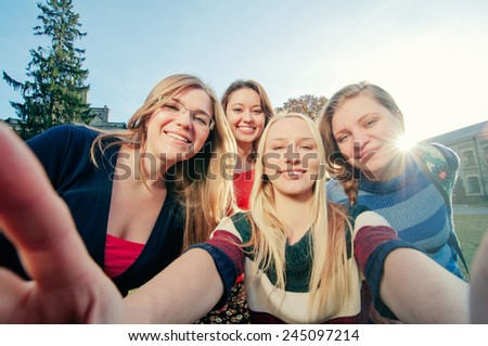 Capturing fun. Student's life. Four young happy women making selfie and smiling outdoors. - stock photo