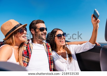 Capturing fun. Three young happy people enjoying road trip in convertible and making selfie - stock photo
