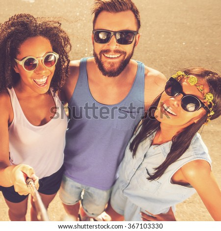 Capturing great time. Top view of three cheerful young people making selfie while standing outdoors together - stock photo