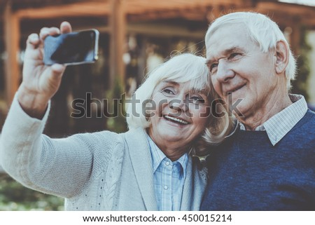 Capturing real love. Happy senior couple bonding to each other and making selfie while standing outdoors - stock photo