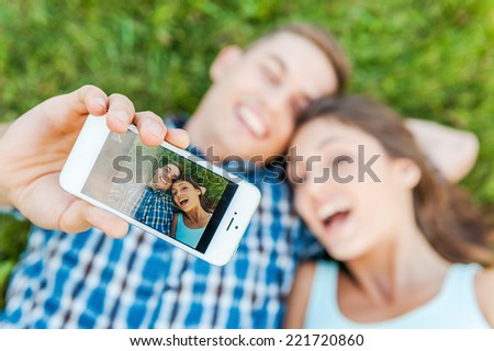 Capturing the bright emotions. Top view of happy young loving couple making selfie with smart phone while lying on the grass. - stock photo