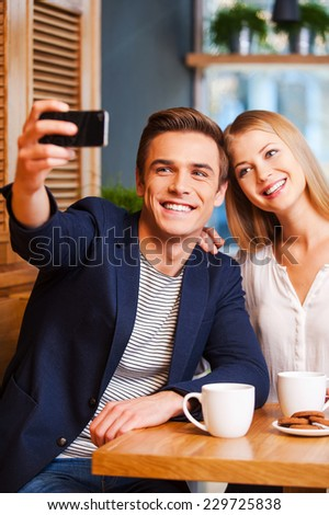 Capturing the bright moments. Beautiful young loving couple bonding to each other in cafe while man making selfie by smart phone - stock photo