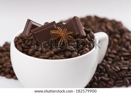 Capuccino cup full of coffee beans - stock photo