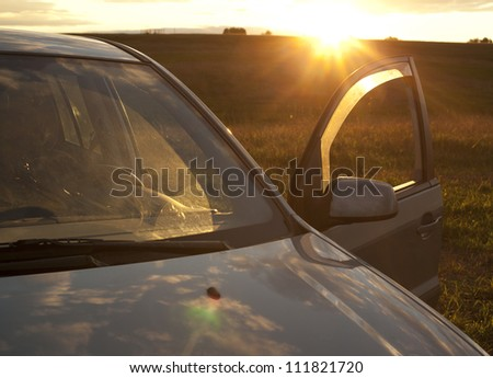 Car against sunset in the background  idea of ??environmentally friendly electric vehicle powered by the solar energy - stock photo