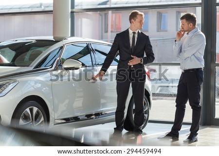 Car agent and customer in car showroom - stock photo