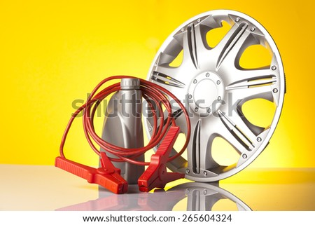 Car alloy wheel, motor oil with  jump start cable isolated on yellow - stock photo