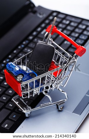 Car and key in shopping trolley above laptop keyboard - stock photo