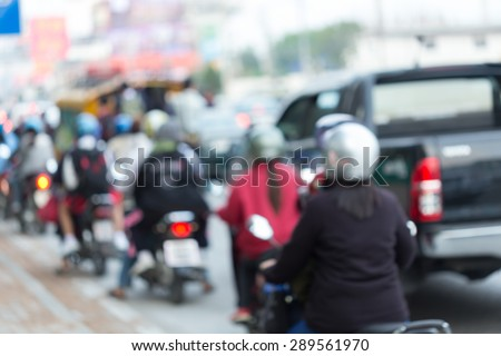 car and motorcycle driving on road with traffic jam in the city, abstract blurred background