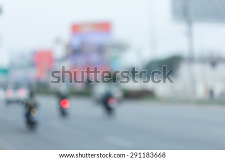 car and motorcycle driving on road with traffic jam in the city, abstract blurred background - stock photo