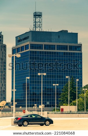 Car and view of highrises from the top of a parking garage in Towson, Maryland. - stock photo