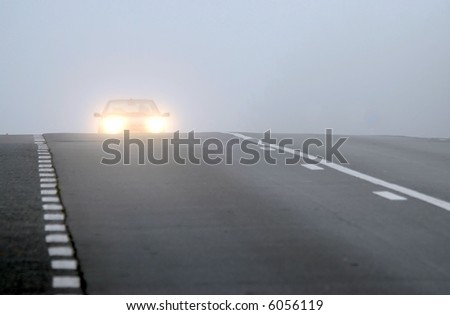 Car appearing through fog with headlights on - stock photo