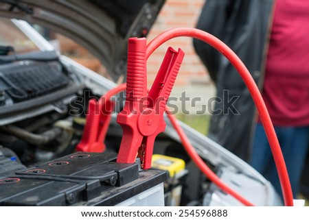 car battery clamped with red  jumper cable to recharge the power - stock photo