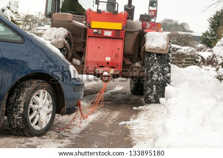 Car being successfully towed back onto the road after being stuck in the snow - stock photo