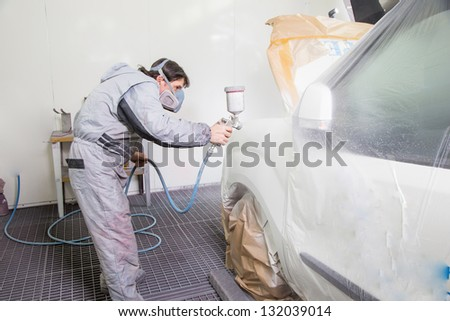 Car body painter spraying paint or color on bodywork in a garage or workshop with an airbrush - stock photo