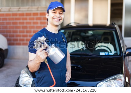 Car body repairer holding a spray gun - stock photo