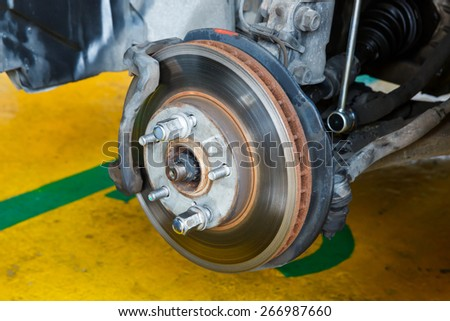 Car brake repairing in garage, automotive service station - stock photo