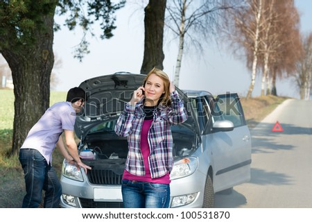 Car breakdown couple calling for road assistance man look engine - stock photo