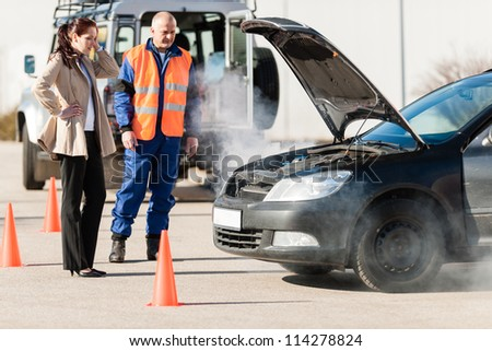 Car breakdown woman get help road assistance man smoking engine - stock photo