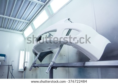 Car bumper befor painting in a cars spray booth. Bumper covered wtith base paint prepared for painting. Car bumper after base paint. Auto vehicle primer bumper. Parts of car in cars spray booth. - stock photo