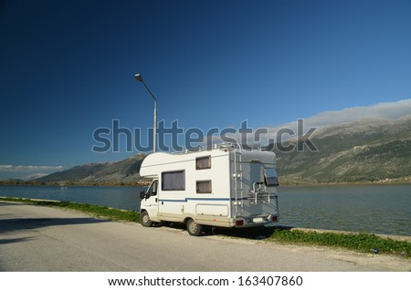 car caravan lake and mountains sunny day - stock photo