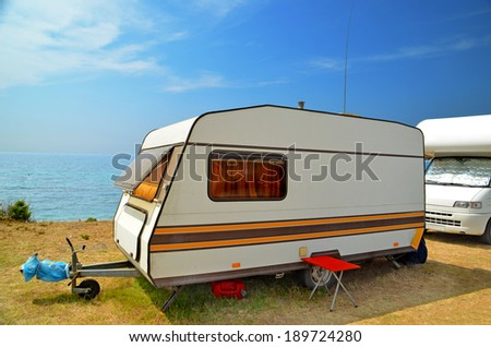 car caravan trailer by the sea - blue sky background - stock photo