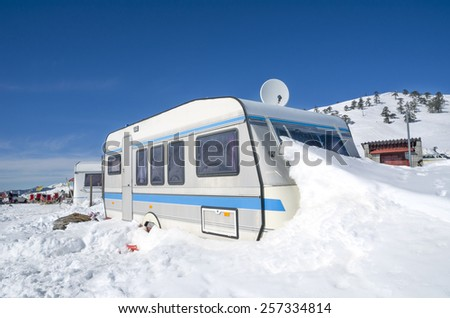 car caravan trailer in the snow - winter holidays, sports events on the ice - stock photo