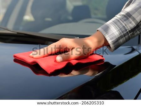 Car care - polishing a black car. - stock photo