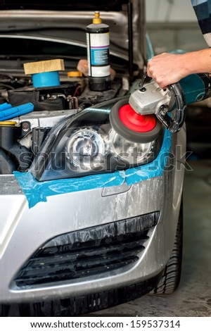 Car Care with Car headlight cleaning with power buffer machine at service station - stock photo