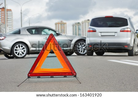 Car collision in city street. Road warning triangle sign at first plane - stock photo