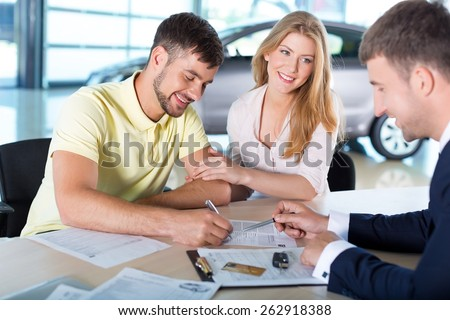 Car. Couple completing paperwork in car showroom  - stock photo