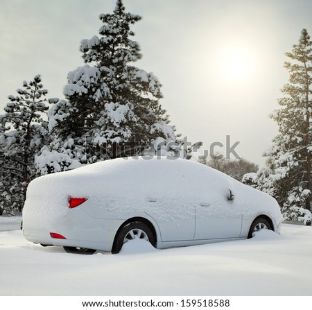 car covered with snow in the forest - stock photo