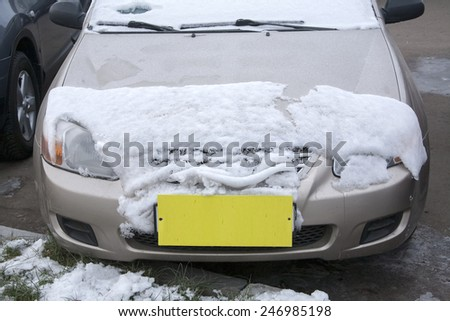 car covered with snow with a yellow label instead of the number