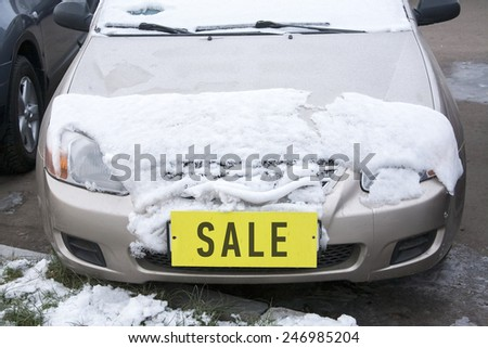 car covered with snow with a yellow label 'sale' instead of the number
