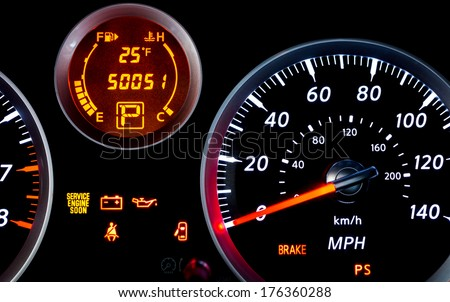Car dashboard with illuminated instrument panel - stock photo