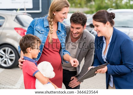 Car dealer advising family on buying auto showing price list - stock photo