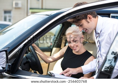 Car dealer and happy smiling woman signing a contract. Concept for car rental  - stock photo