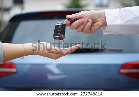 car dealer gives the customer the car keys with car in background - stock photo