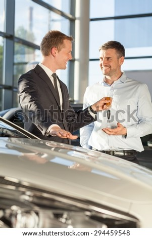 Car dealer giving client keys of his new car - stock photo