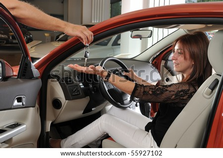 Car dealer giving keys of a new car to happy customer - a series of BUYING A NEW CAR images. - stock photo