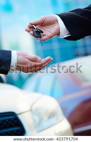 Car dealer giving keys to buyer - stock photo