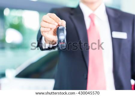 Car dealer handing over auto key - stock photo