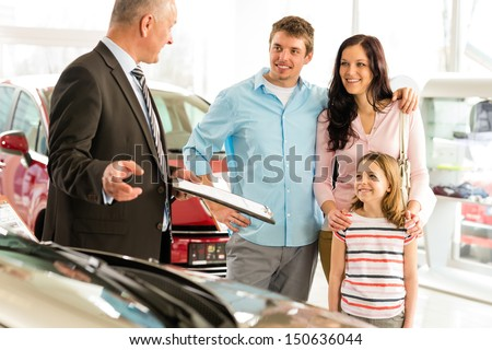 Car dealer offering a car to smiling family - stock photo