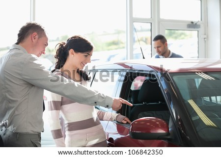 Car dealer pointing the interior of a car with a woman in a car shop - stock photo