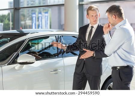 Car dealer showing vehicle to mature man - stock photo