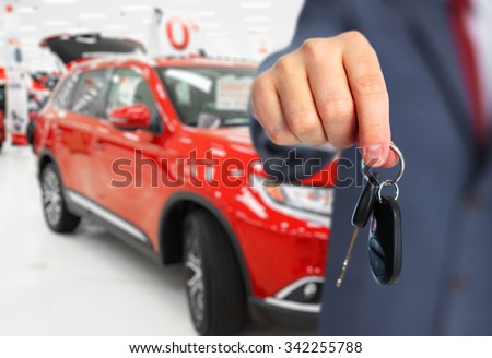 Car dealer with a key. Auto dealership and rental concept background.