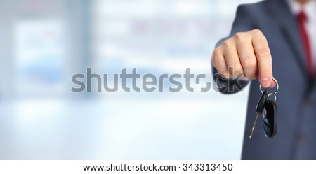 Car dealer with a key. Auto dealership and rental concept background. - stock photo