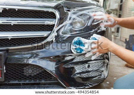 Car detailing series : Closeup of hand cleaning black car of serviceman.