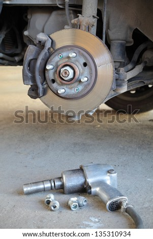 Car disc brakes and pneumatic wrench tool - stock photo