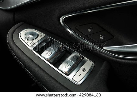 Car door interior armrest with window control panel, door lock button. Interior details. - stock photo